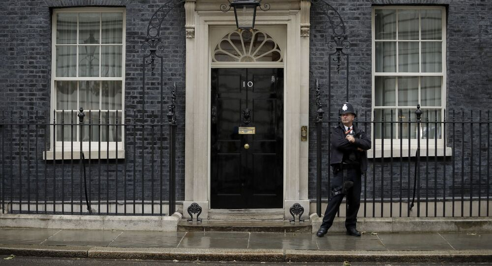 A police officer stands guard outside the door of 10 Downing Street in London, Friday, June 7, 2019