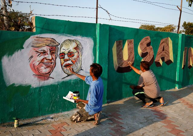 A man applies finishing touches to paintings of U.S. President Donald Trump and India's Prime Minister Narendra Modi on a wall as part of a beautification along a route that Trump and Modi will be taking during Trump's upcoming visit, in Ahmedabad, India, February 17, 2020