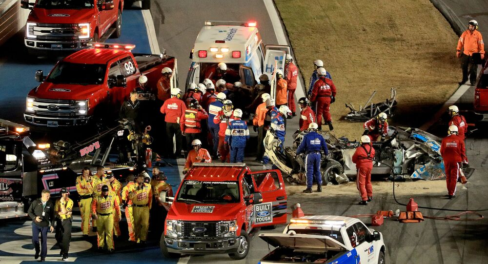 Track workers attend to Ryan Newman, driver of the #6 Koch Industries Ford, following a crash during the NASCAR Cup Series 62nd Annual Daytona 500