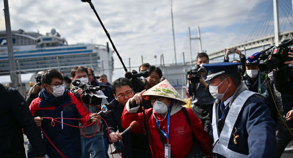 passenger (C) leaves on foot after dismembarking the Diamond Princess cruise ship in quarantine due to fears of the new COVID-19 coronavirus, at the Daikoku Pier Cruise Terminal in Yokohama on February 19, 2020