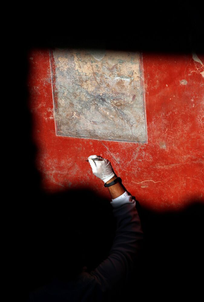 An archaelogist works on a fresco in the House of Lovers Casa degli Amanti, one of three restored domus (ancient houses) reopened to the public at the archaeological site of Pompeii, Italy, 18 February 2020.