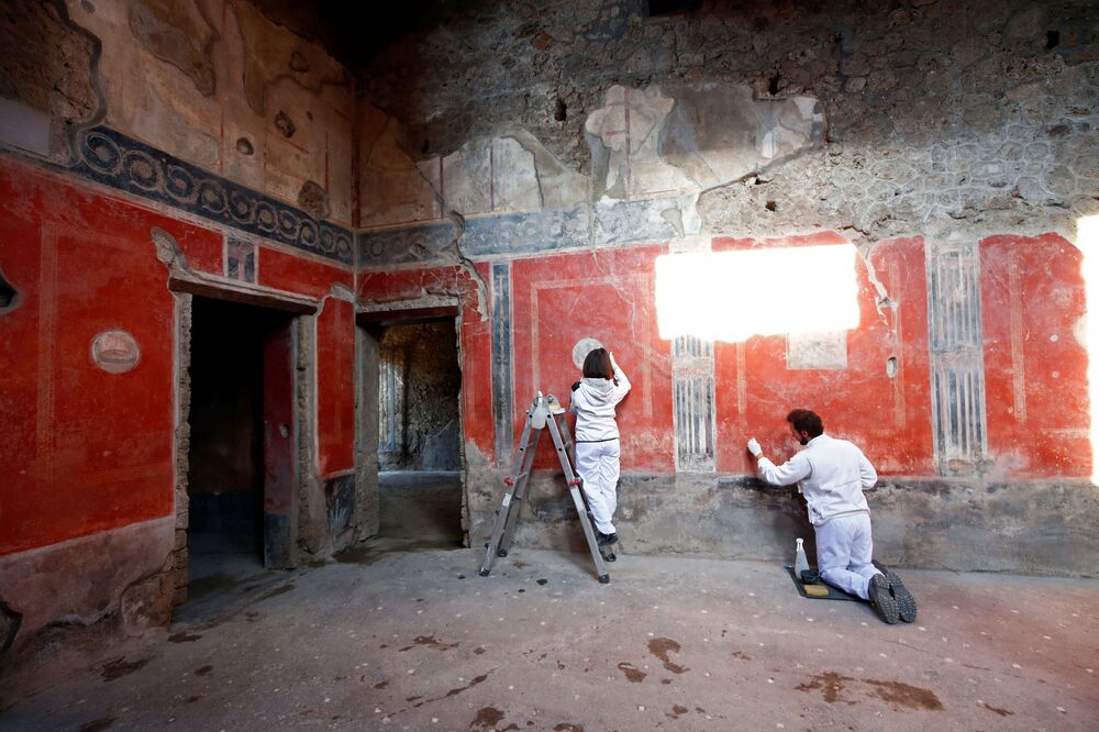Archaeologists work on  a fresco in the House of Lovers Casa degli Amanti,one of three restored domus (ancient houses) reopened to the public at the archaeological site of Pompeii, Italy, 18 February 2020.