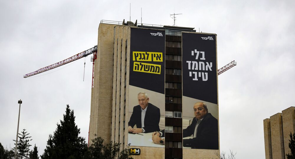 A giant poster showing retired Israeli army general and leader of the Blue and White Israeli electoral alliance Benny Gantz (L) and Arab Israeli member of the Joint List Ahmad Tibi, with a writing in Hebrew that reads:Without Ahmed Tibi, Gantz doesn't have a government, covers the wall of a building in Jerusalem on February 14, 2020.