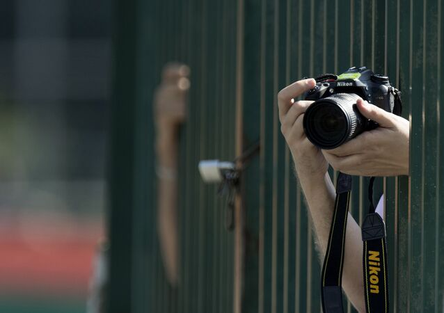 A photographer takes pictures with a Nikon D7100 camera during the third practice session at the Spa-Francorchamps circuit in Spa on August 27, 2016 ahead of the Belgian Formula One Grand Prix