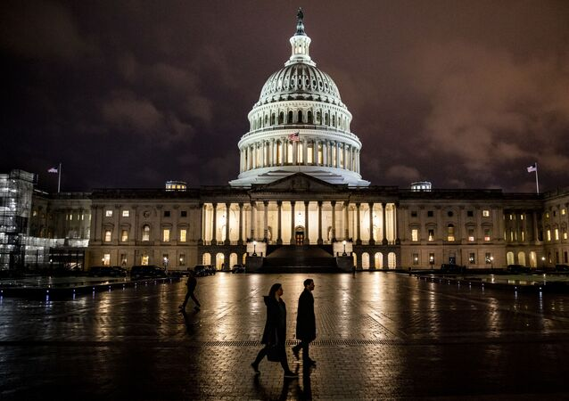 People walk along the east front plaza of the US Capitol as night falls on December 17, 2019 in Washington, DC