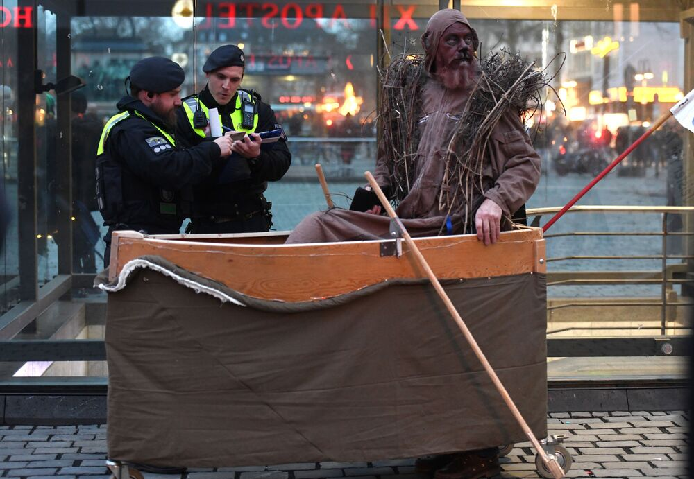 Police officers talk to a protestor in a boat during a demonstration for better climate at the carnival procession 'Geisterzug' in Cologne, western Germany on February 15, 2020.
