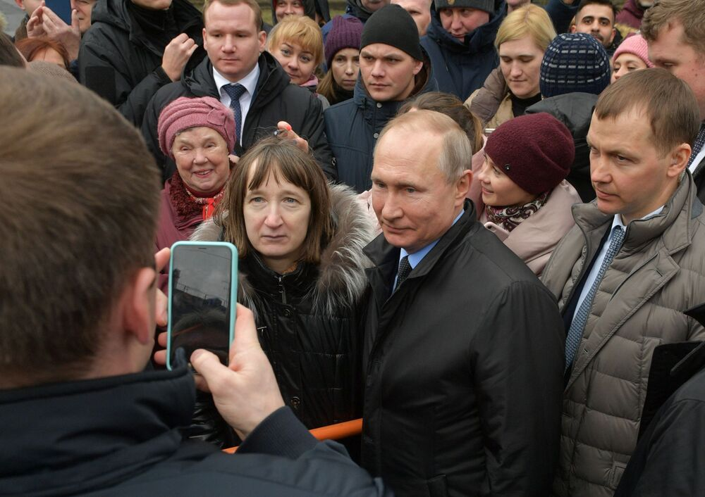 Russian President Vladimir Putin poses for pictures with citizens of Saint Petersburg after laying flowers to the city's first mayor Anatoly Sobchak's monument on 19 February