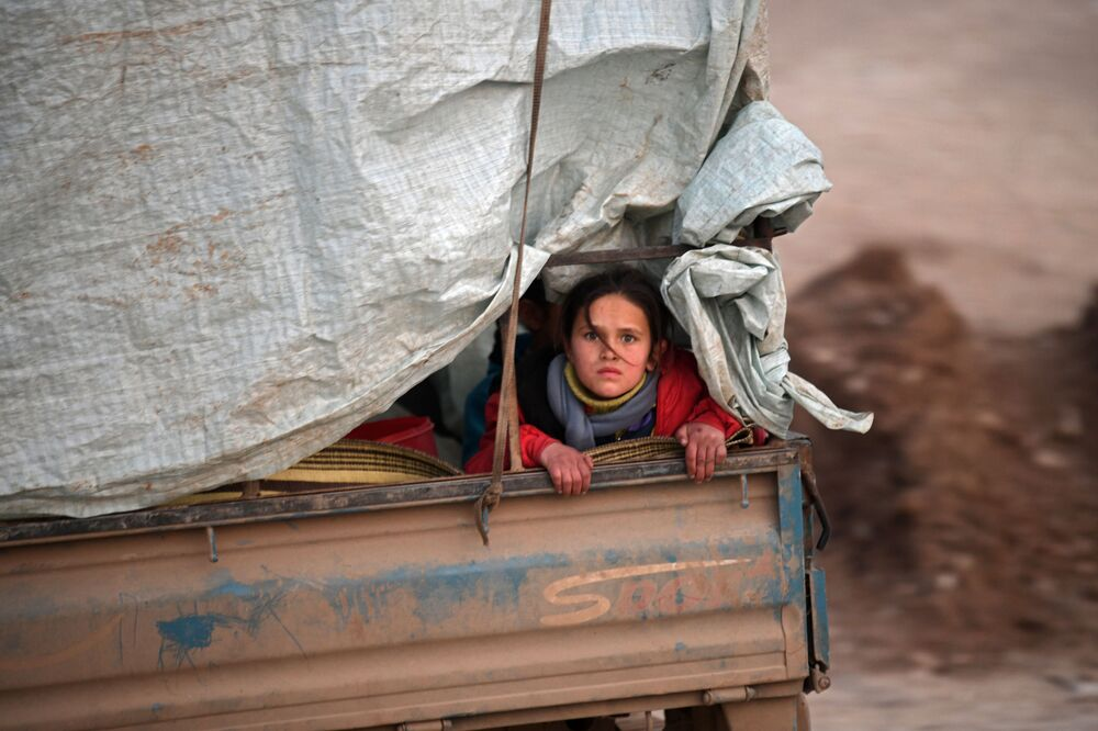 A displaced Syrian girl rides in the back of a truck on the way to Deir al-Ballut camp in Afrin's countryside along the border with Turkey, on February 19, 2020 after fleeing regime offensive on the last major rebel bastion in the country's northwest.