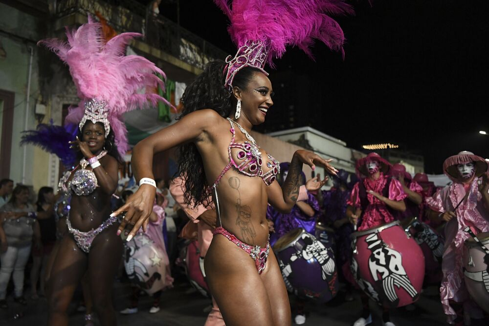 Drummers and dancers forming part of a group known as a comparsa compete by playing and dancing to the rhythm of the traditional candombe music, in Montevideo on February 14, 2020, during the Llamadas, one of the events that make up Uruguay's carnival -- the world's longest.