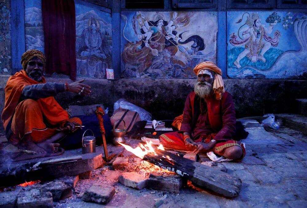 Hindu holy men, or sadhus, sit beside the fire at the premises of Pashupatinath Temple a day ahead of the Shivaratri festival in Kathmandu, Nepal February 20, 2020.