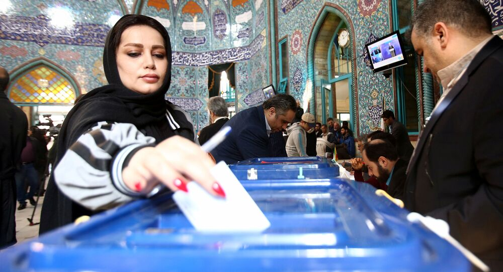 A woman casts her vote during parliamentary elections at a polling station in Tehran, Iran February 21, 2020
