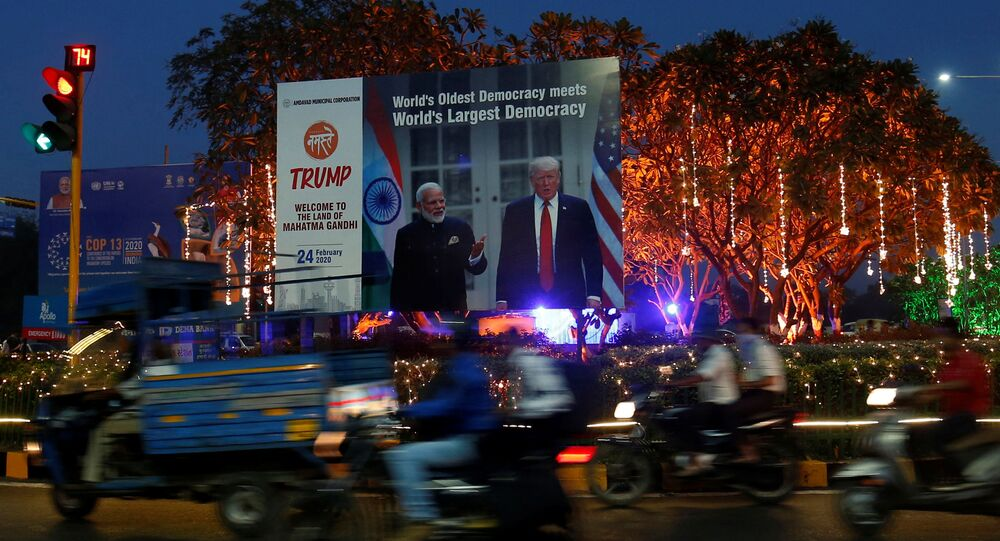 People ride their motorbikes past a hoarding with the images of India's Prime Minister Narendra Modi and U.S. President Donald Trump installed next to decorated trees alongside a road ahead of Trump's visit, in Ahmedabad, India, February 20, 2020