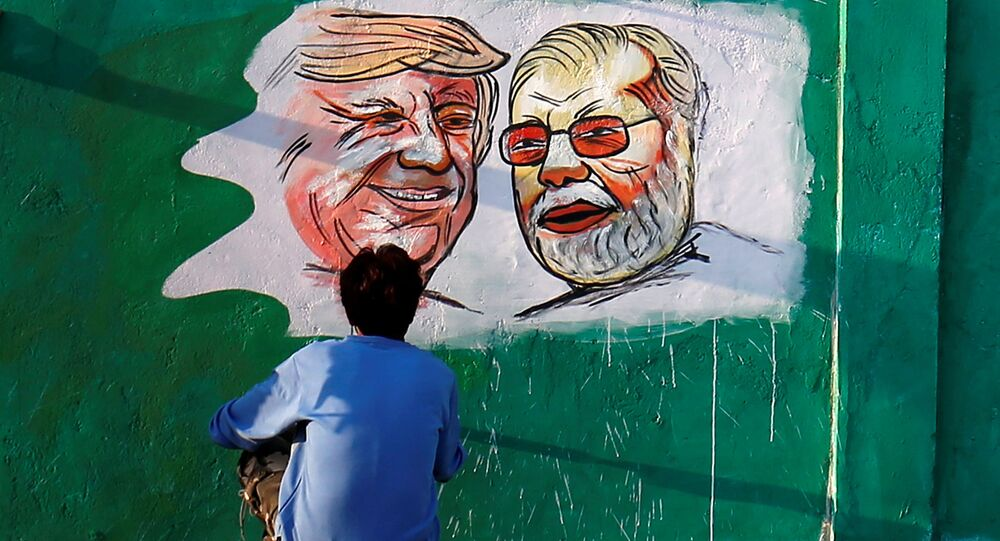 A man applies finishing touches to paintings of US President Donald Trump and India's Prime Minister Narendra Modi on a wall as part of a beautification project along a route that Trump and Modi will be taking during Trump's upcoming visit, in Ahmedabad, India, 17 February 2020.