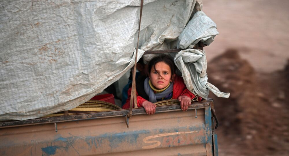 A displaced Syrian girl rides in the back of a truck on the way to Deir al-Ballut camp in Afrin's countryside along the border with Turkey, on February 19, 2020