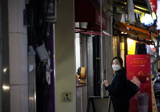 A woman wearing a mask to prevent contracting the coronavirus waits for her food at Dongseong-ro shopping street in central Daegu, South Korea February 21, 2020