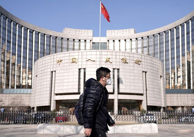 A man wearing a mask walks past the headquarters of the People's Bank of China, the central bank, in Beijing, China, as the country is hit by an outbreak of the new coronavirus, February 3, 2020