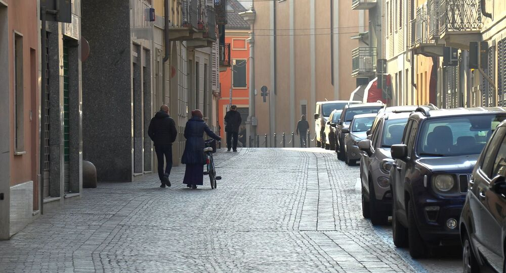 People walk down an empty street in the village of Codogno after officials told residents to stay home and suspend public activities as 14 cases of coronavirus are confirmed in northern Italy, in this still image taken from video in the province of Lodi, Italy, February 21, 2020.