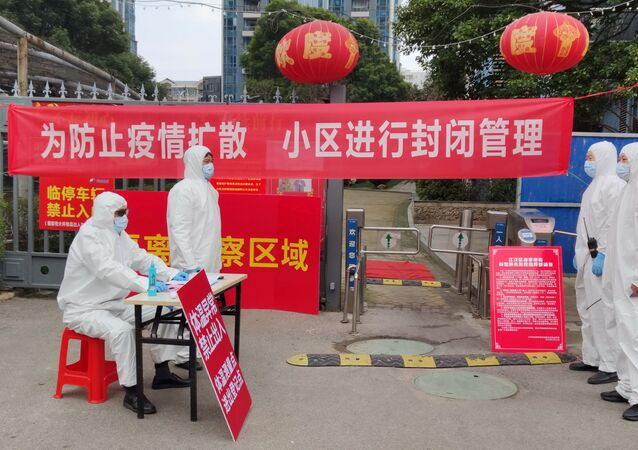 Workers in protective suits are seen at a checkpoint for registration and body temperature measurement, at an entrance to a residential compound in Wuhan, February 13, 2020