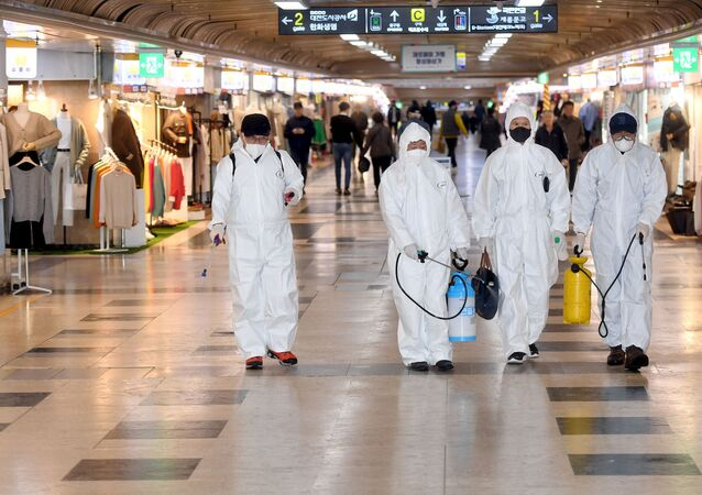 Employees from a disinfection service company sanitize the floor of a shopping center in Daejeon, South Korea, February 22, 2020