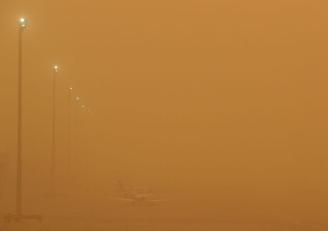 Planes are seen parked on the tarmac during a sandstorm