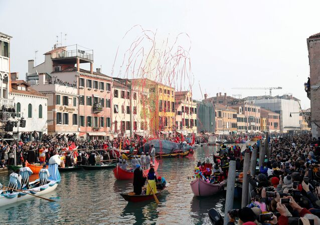 Venetians row along the Grand Canal during during the masquerade parade in Venice, Italy, 9 February 2020.