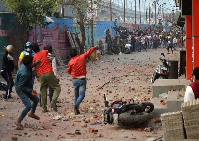 People supporting a new citizenship law and those opposing the law, throw stones at each other during a clash in Maujpur area of New Delhi, India, February 23, 2020.