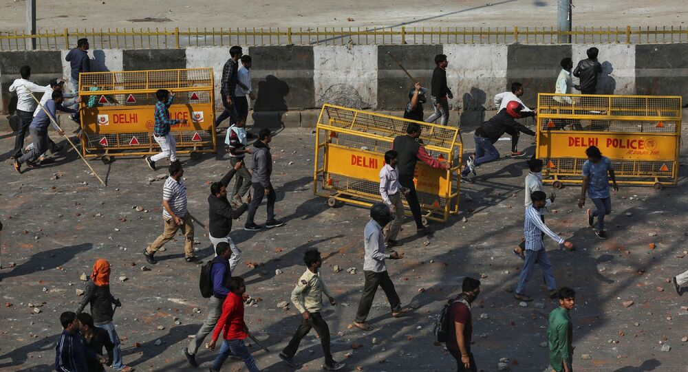 People supporting a new citizenship law and those opposing the law, clash during a protest in New Delhi