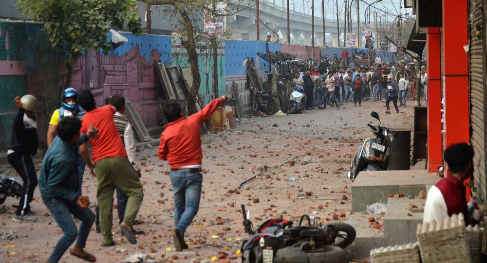 People supporting a new citizenship law and those opposing the law, throw stones at each other during a clash in Maujpur area of New Delhi, India, February 23, 2020