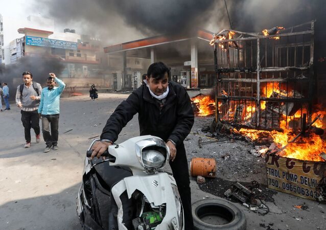 A man pushes his damaged scooter past a burning petrol pump during a clash between people supporting a new citizenship law and those opposing it, in New Delhi India, February 24, 2020