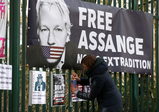 A supporter of WikiLeaks founder Julian Assange posts a sign on the Woolwich Crown Court fence, ahead of a hearing to decide whether Assange should be extradited to the United States, in London, Britain February 25, 2020.