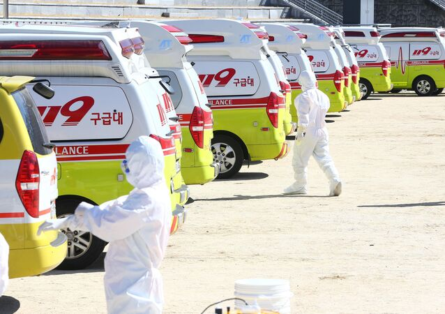Medical workers get ready as ambulances are parked to transport a confirmed coronavirus patient in Daegu, South Korea, February 23, 2020