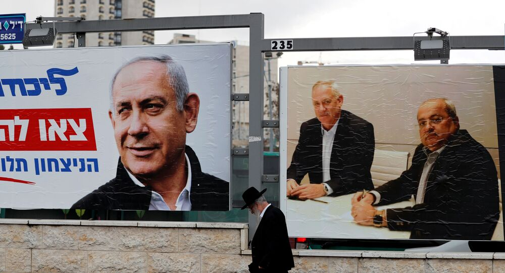 An ultra-Orthodox Jewish man walks next to Likud party election campaign banners, one depicting party leader Israeli Prime Minister Benjamin Netanyahu and the other depicting Benny Gantz, head of Blue and White party and Ahmad Tibi, co-leader of the Joint List, an Arab party, in Jerusalem February 20, 2020