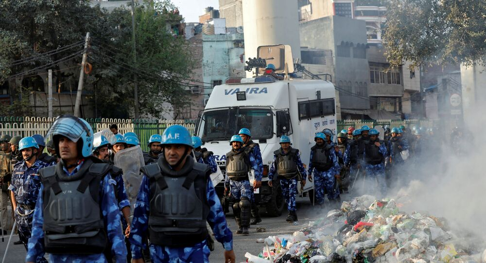Members of Rapid Action Force (RAF) move past smoldering debris after it was set on fire by demonstrators in a riot affected area after fresh clashes erupted between people demonstrating for and against a new citizenship law in New Delhi, India, February 25, 2020.