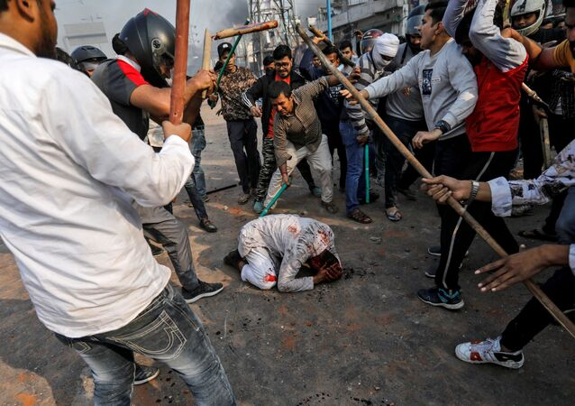 People supporting the new citizenship law beat a Muslim man during a clash with those opposing the law in New Delhi, India, February 24, 2020