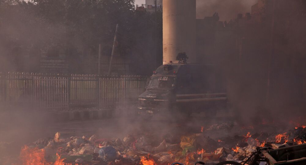 A police vehicle moves past burning debris that was set on fire by demonstrators in a riot affected area after fresh clashes erupted between people demonstrating for and against a new citizenship law in New Delhi, India, February 25, 2020.