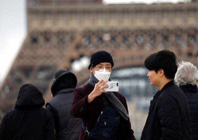 A man wears a face mask on the Trocadero esplanade in front of the Eiffel Tower in Paris, France, February 26, 2020