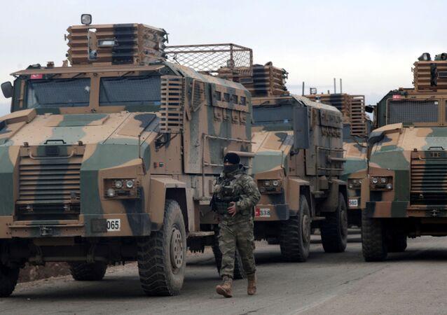 A Turkish soldier walks near Turkish military vehicles in Hazano near Idlib, Syria, February 11, 2020