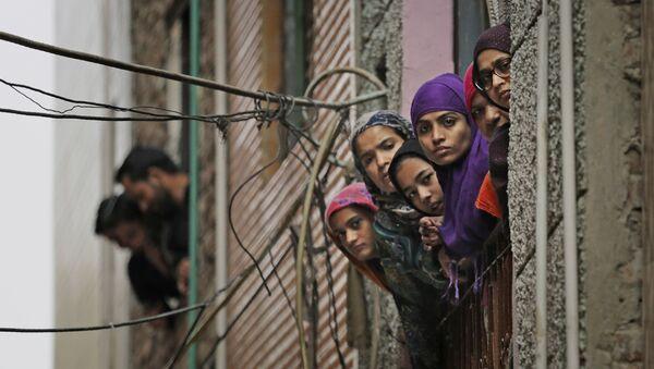 Indian Muslim women look out of a window as security officers patrol a street in New Delhi - Sputnik International