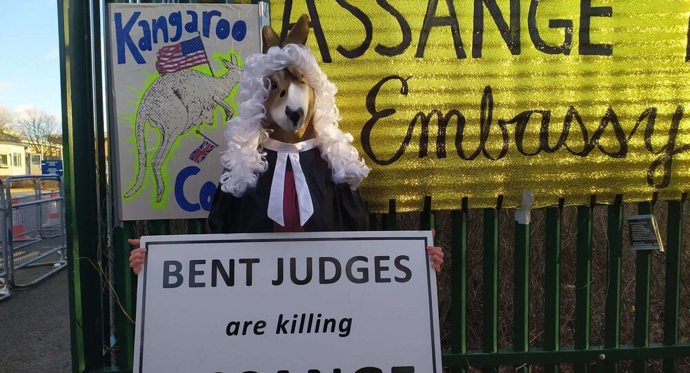 Woman holds sign outside of Belmarsh which says Bent Judges Are Killing Assange