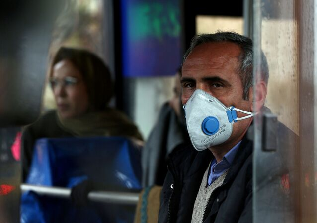 An Iranian man wears a protective masks to prevent contracting coronavirus, as he sits in the bus in Tehran, Iran 25 February 2020.
