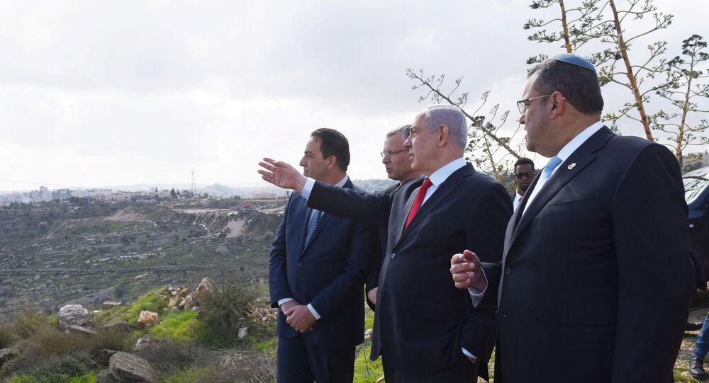 Israeli Prime Minister Benjamin Netanyahu points to the area of Israeli settlement of Har Homa, located in an area of the Israeli-occupied West Bank, that Israel annexed to Jerusalem after the region's capture in the 1967 Middle East war, February 20, 2020