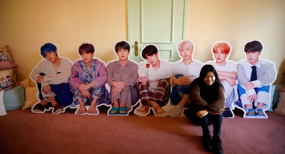 A fan of K-pop idol boy band BTS poses for photographs with cut-out of BTS at a pop-up store selling BTS goods in Seoul, South Korea, December 24, 2019.