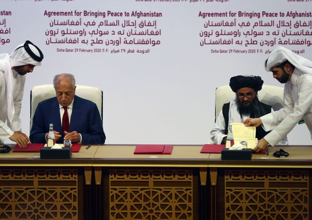 Mullah Abdul Ghani Baradar, the leader of the Taliban delegation, signs an agreement with Zalmay Khalilzad, U.S. envoy for peace in Afghanistan, at a signing agreement ceremony between members of Afghanistan's Taliban and the U.S. in Doha, Qatar February 29, 2020.