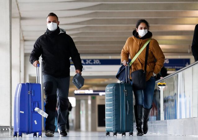 People wearing protective face masks walk as they arrive at Charles de Gaulle airport near Paris, France, as the coronavirus outbreak continues to expand, February 29, 2020.