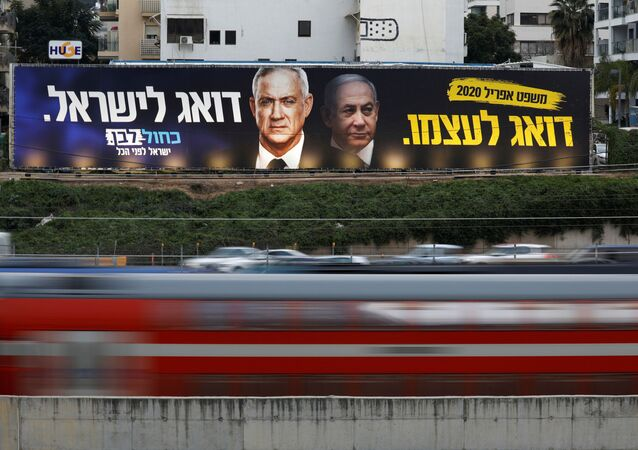 Traffic moves past a Blue and White party election campaign poster, depicting party leader Benny Gantz, and Israeli Prime Minister Benjamin Netanyahu, in Tel Aviv, Israel February 18, 2020.