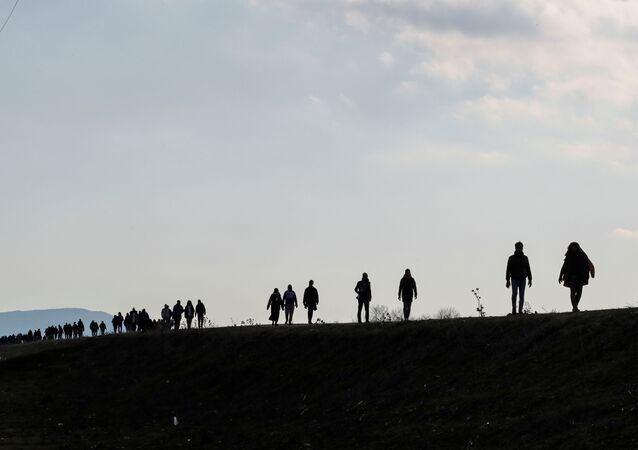Migrants walk along a road, parallel to the border line, to reach Greece as they are pictured near Karpuzlu village of the Turkish border city of Edirne, Turkey, March 1, 2020.