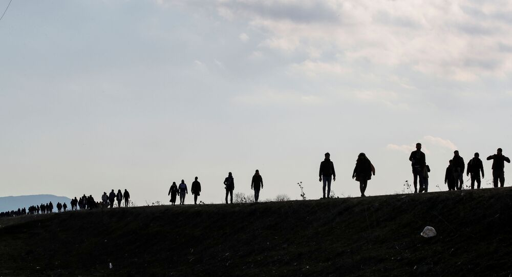 Migrants walk along a road, parallel to the border line, to reach Greece as they are pictured near Karpuzlu village of the Turkish border city of Edirne, Turkey, 1 March 2020.