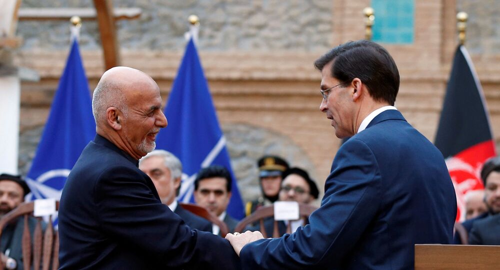 Afghanistan's President Ashraf Ghani shakes hands with U.S. Defense Secretary Mark Esper, during a news conference in Kabul, Afghanistan February 29, 2020.