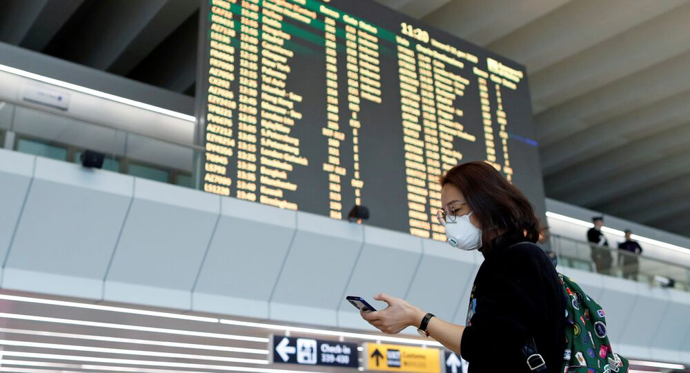 FILE PHOTO: A passenger in a protective mask uses her phone at Rome's Fiumicino airport, after first cases of coronavirus were confirmed in Italy, January 31, 2020. REUTERS/Yara Nardi/File Photo
