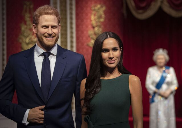 The figures of Britain's Prince Harry and Meghan, Duchess of Sussex, left, are moved from their original positions next to Queen Elizabeth II, Prince Philip and Prince William and Kate, Duchess of Cambridge, at Madame Tussauds in London, Thursday Jan. 9, 2020.